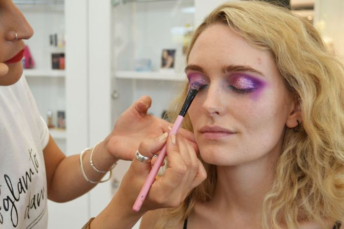 9 - Close up of purple make up being applied to a models eyelids